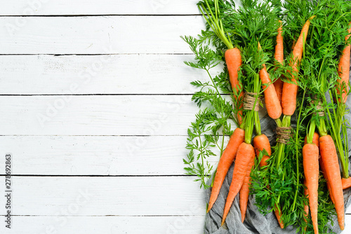 Obraz Fresh carrots on a white wooden background. Top view. Free space for your text. - fototapety do salonu
