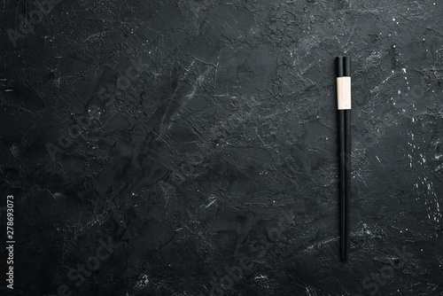 Wooden chopsticks on a black stone background. Top view. Free space for your text. - 278693073