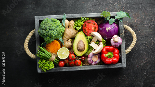 Fresh vegetables in a wooden box. Vegetarian food. Top view. Free space for your text.