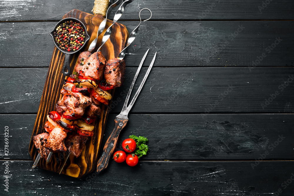Fototapety, obrazy: Shish kebab BBQ meat with onions and tomatoes. On a black background. Top view. Free space for your text. Rustic style.