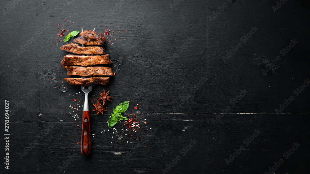 Fototapety, obrazy: Pork steak on the fork. On a wooden background. Top view. Free space for your text.