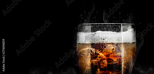 Fotografía  Soft drink glass with ice splash on cool smoke background