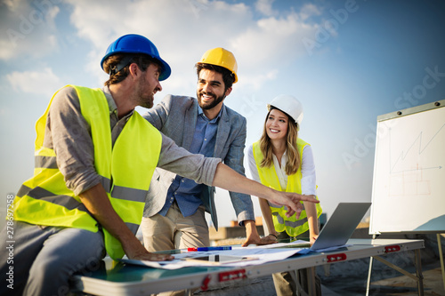 Fotografiet Team of architects and engineer in group on construciton site check documents an