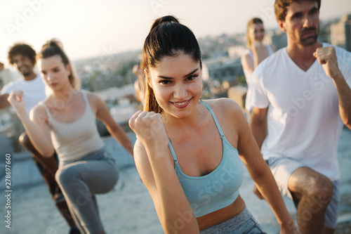 Fitness, sport, friendship and healthy lifestyle concept . Group of happy people exercising