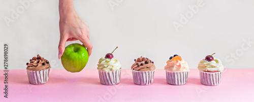 Fototapeta apple among cupcakes, healthy food choices, female hand picks green apple, fatty sweet food, diet, weight loss obraz