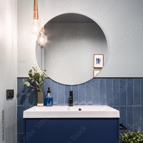 Bathroom with big round mirror