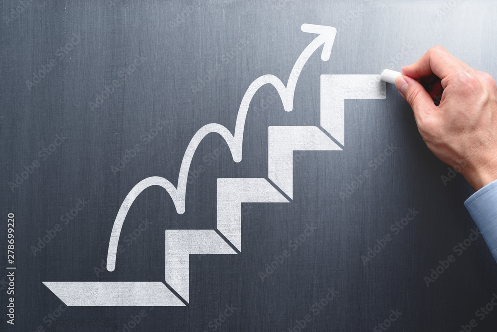 Fototapeta Steps to succeed in business. Businessman drawing steps and arrow on chalkboard.