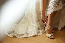 Bride Puts On Wedding Shoes On High Heels