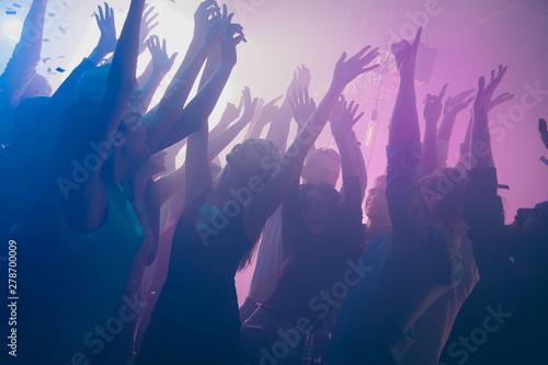 Obraz Close up photo of many birthday party people dancing clubbing purple lights confetti fog nightclub hands raised shiny formal-wear - fototapety do salonu