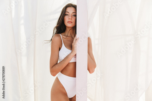 Obraz Portrait of gorgeous caucasian woman in swimsuit standing over white curtains at beach - fototapety do salonu
