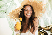 Photo Of Beautiful Brunette Woman In Straw Hat And Summer Clothes Drinking Orange Juice In Beach Cafe