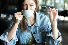 Young Woman Drinking Coffee Sm...