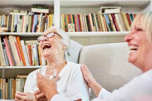 Fotografiet Altenpflegerin und Senior Frau lachen zusammen