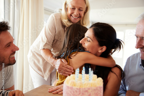 Photo Mid adult woman embracing her daughter after blowing out candles on birthday cak