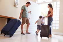 Mid Adult White Couple And Kids Leaving Their Home With Luggage To Go On Vacation, Full Length