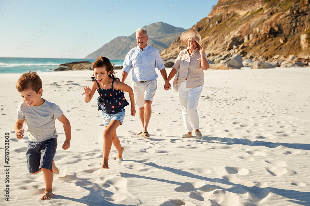 Fototapety, obrazy: Senior white couple and their grandchildren walking on a sunny beach, close up