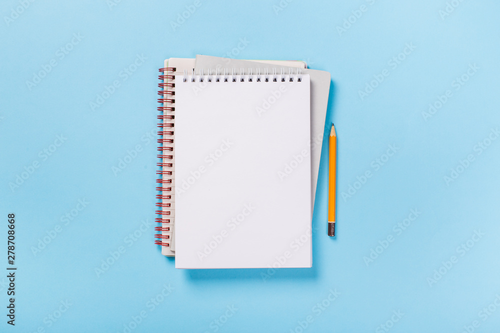 Fototapeta school notebook on a blue background, spiral notepad on a table