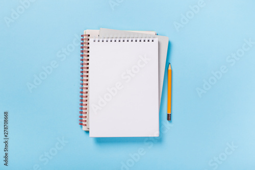 school notebook on a blue background, spiral notepad on a table Fototapet