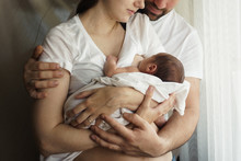 Father And Mother With A Newborn Son. New Young Multi-generation Family. Breast-feeding