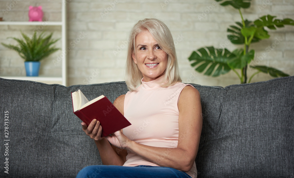 Fototapety, obrazy: Happy middle aged woman is reading a book at home