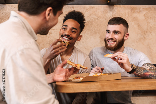 Fototapety, obrazy: Three cheerful men eating pizza at the cafe table