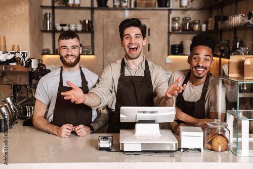Happy coffee men colleagues in cafe bar working indoors.