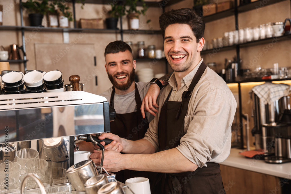Fototapeta Group of cheerful men baristas wearing aprons