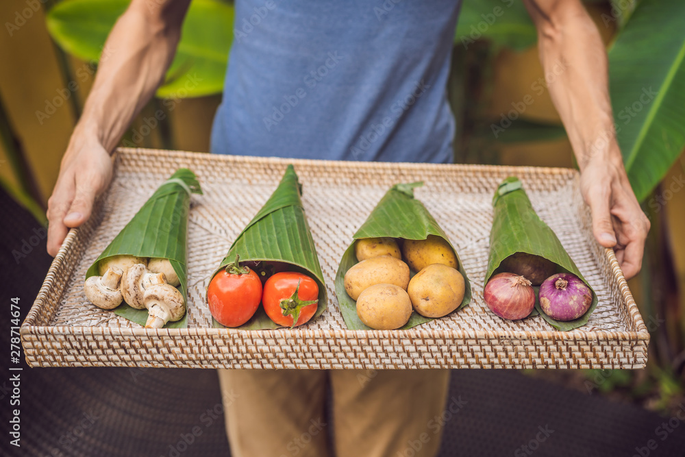 Fototapety, obrazy: Eco-friendly product packaging concept. Vegetables wrapped in a banana leaf, as an alternative to a plastic bag. Zero waste concept. Alternative packaging