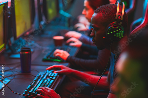 Fotografía Group of serious focused multi-ethnic gamers sitting in row and playing video ga