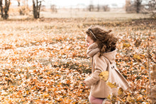 Cute Little Girl With Curly Hair Rejoices In Autumn, Running Through The Fallen Leaves