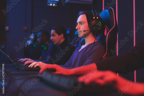 Photo  Serious concentrated gamers in headphones for online communication sitting in da