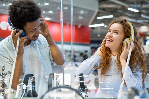 Photo Stands Music store African guy with red-haired girl in an electronics store listening to music in headphones choosing before buying