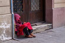 Homeless Leaning Against Barn Door.