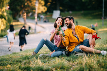 Young Happy Couple Enjoying A Park With Beer In Hand During The Summer