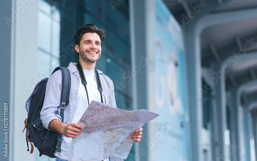 Cheerful man traveler holding map, studying new destinations at airport Canvas