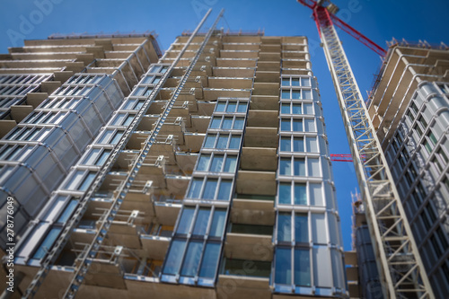 Poster London High-rise building under construction. The site with cranes against blue sky. Tilt shift focus