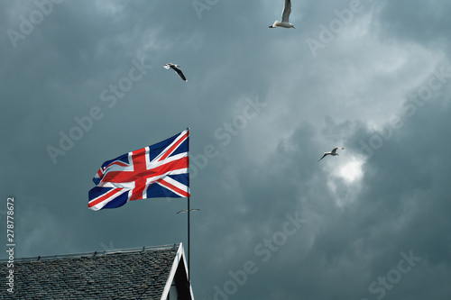British flag fluttering in the wind on the roof of a house amid clouds and flyin Canvas Print