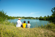 Two Boys With Fishing Rods Catch Fish On The Pond With A Grandfather.