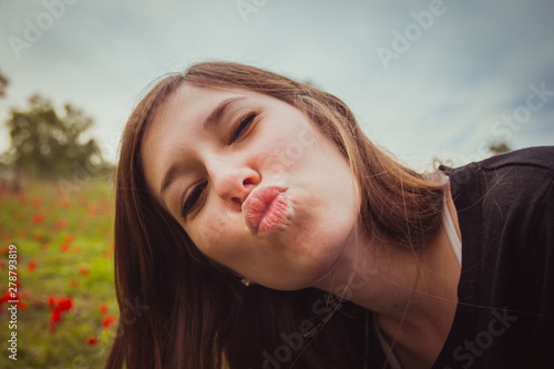 Young woman making duckface kiss while taking selfie picture with her smartphone Canvas Print