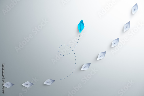 Fotografía  Group of white paper ship in one direction and one blue paper ship pointing in different way on white background