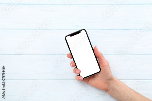 Valokuva  Smartphone in female hand on wooden background