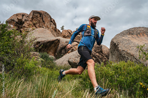 Obraz Male runner running on a mountain trail - fototapety do salonu