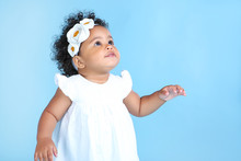 Beautiful Baby Girl In White Dress On Blue Background