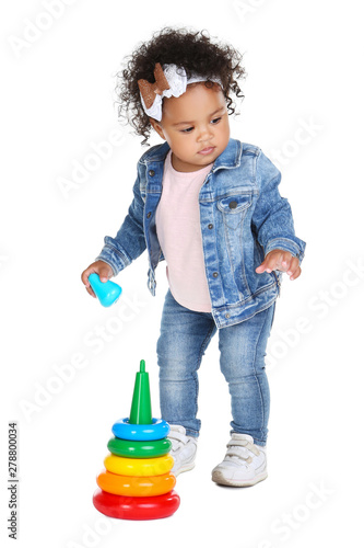 Photo Beautiful baby girl with rainbow toy on white background