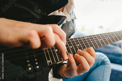 Detail of the fingers of a guitarist placed on the fret of the mast of the guitar playing a chord doing Tapping Fototapet