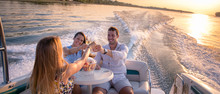 Friends Are Drinking On A Boat In Sunset