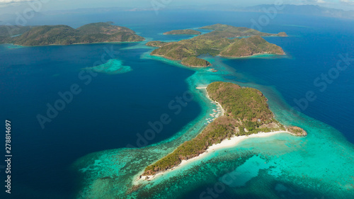 aerial view tropical islands with blue lagoons, coral reef and sandy beach. Palawan, Philippines. Islands of the Malayan archipelago with turquoise lagoons.