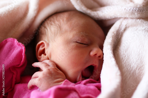 Photo Cute newborn baby in pink baud with an open mouth on her bed under beige blanket