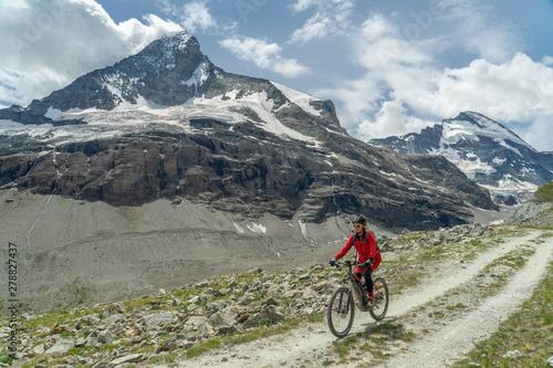 active senior woman, riding her electric mountainbike below the famous Matterhorn in Zermatt, Wallis,Switzerland #278827437