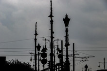 Jumble Of Victorian Style Gas Street Lamps, Modern Road Signs And Overhead Wires And Tram Cables Silhouetted Against A Background Of Storm Clouds